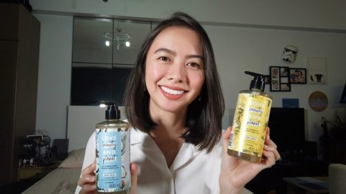 holding two bottles of the love beauty and planet hand wash