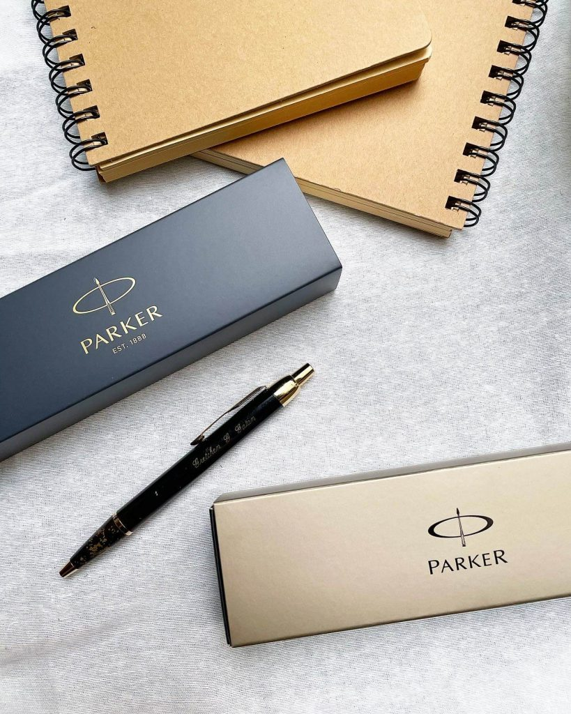 gold and black parker ballpen with notebooks